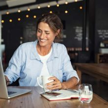 A smiling woman working at a laptop and drinking a coffee